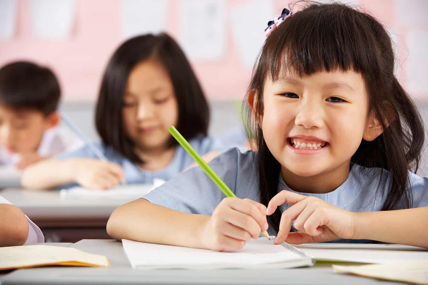 Girl studying and smiling for the camera in a good tuition centre